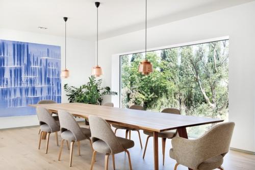 En el comedor destacan la mesa rectangular de nogal Cena, de Zeitraum, y las sillas Conference, un diseño de Eero Saarinen que edita Knoll. Las lámparas de suspensión Utzon JU1 son de Jørn Utzon, producidas por &Tradition.