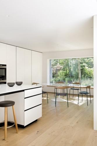 Cocina, de Artificio. Taburetes en roble y piel CH56, y sillas de office CH88, de acero lacado, tapizadas y con respaldo de roble, diseño de Hans J. Wegner que edita Carl Hansen & Søn. La mesa Tulip, creación de Eero Saarinen, es de Knoll.