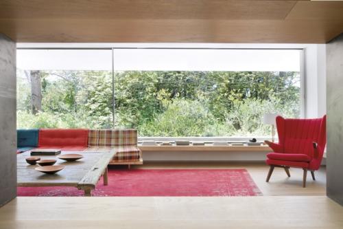 Uno de los salones, con el sofá Mah Jong, de Hans Hopfer para Roche Bobois, y una mesa de centro en madera de teca de Indonesia, que en sus inicios se empleó como telar. La butaca roja retapizada Skipper es un diseño de Svend Skipper. Ambas, en Batavia.